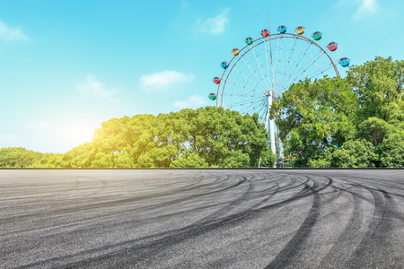Asphalt square road and ferris wheel with green forest landscape