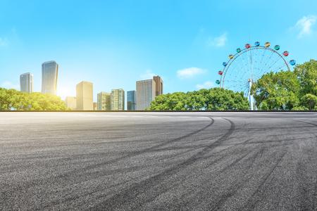 Empty asphalt road ground and modern building with ferris wheel 版權商用圖片