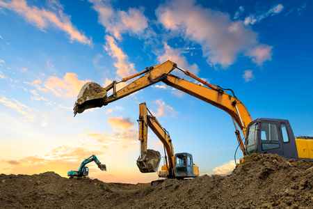 Three excavators work on construction site at sunset Stock Photo