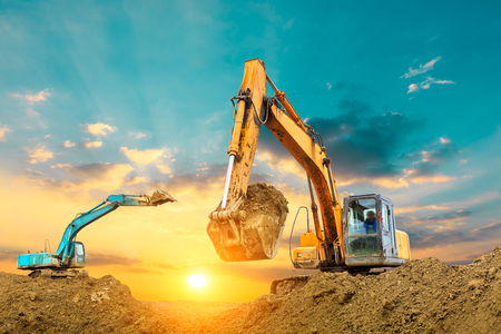 Two excavators work on construction site at sunset Stock Photo