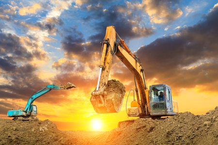 Two excavators work on construction site at sunset