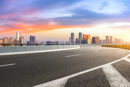 Empty asphalt road and city skyline at sunrise in hangzhou