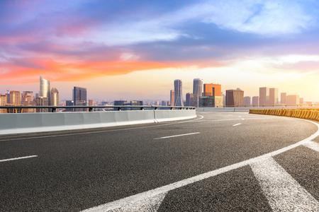 Leere Asphaltstraße und Skyline der Stadt bei Sonnenaufgang in Hangzhou
