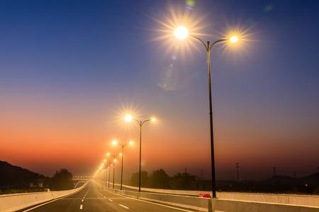 Stadtstraße und helle Straßenlaternenlandschaft bei Sonnenuntergang