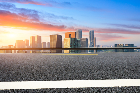 Empty asphalt road and city skyline in Hangzhou at sunrise,high angle view