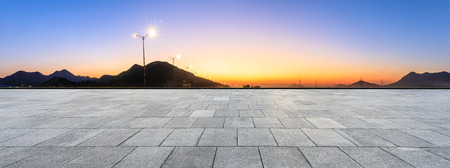 Empty square floor and mountain silhouette at beautiful sunset