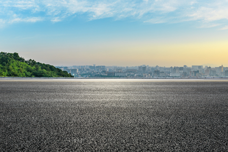 Panoramic city skyline and buildings with empty asphalt road at sunrise