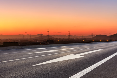 Asphalt road and hills at beautiful sunset