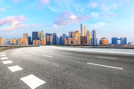 Carretera de asfalto vacía y horizonte de la ciudad moderna con edificios en Hangzhou