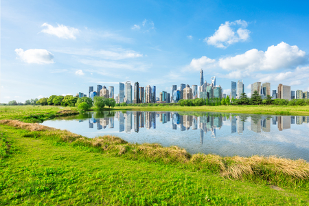 Shanghai city skyline and green grass with lake under the blue sky,China