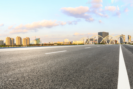 Asphalt road and city skyline with bridge construction in shanghai at sunset