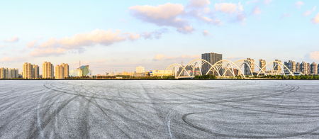 Asphalt race track ground and city skyline panorama with bridge construction in shanghai at sunset Stockfoto