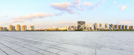 Empty square floor and city skyline panorama with bridge construction in shanghai at sunset
