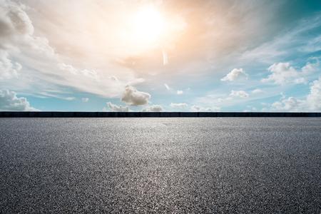 Route goudronnée vide et beaux nuages de ciel au coucher du soleil
