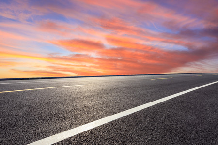 Empty asphalt road and sunset clouds
