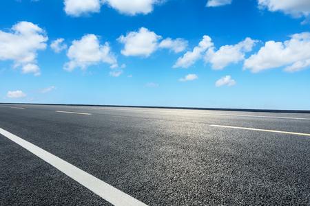 Carretera de asfalto vacía y cielo azul con escena de nubes blancas Foto de archivo
