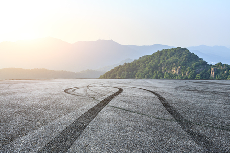 Empty asphalt race track ground and mountains landscape