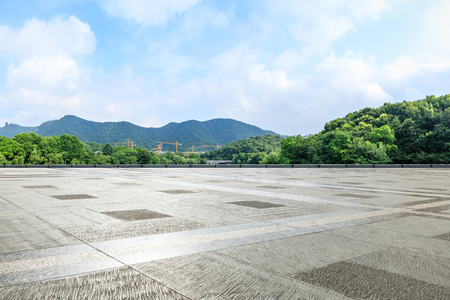 Empty square floor and green mountain with sky landscape