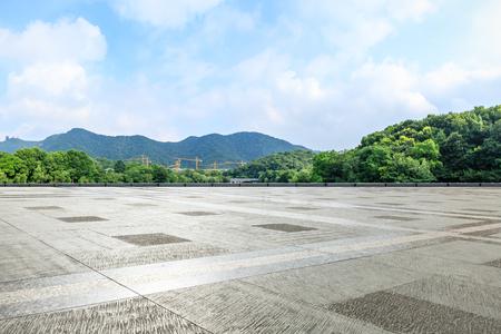 Piso cuadrado vacío y montaña verde con paisaje de cielo
