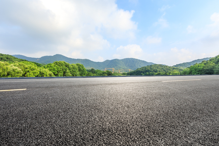 Empty asphalt road and mountains with blue sky on a sunny day Standard-Bild