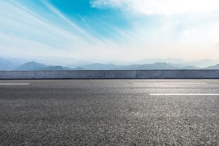 Pusta asfaltowa droga i góry z pięknym krajobrazem chmur