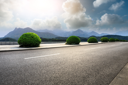 Empty asphalt road and mountains with clouds landscape