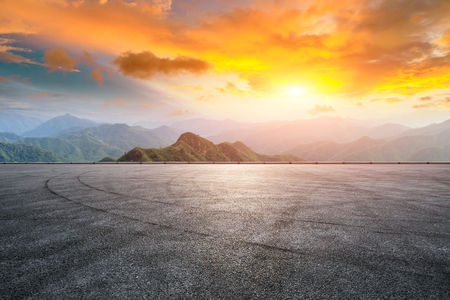 Asphalt race track ground and mountain with sunset clouds