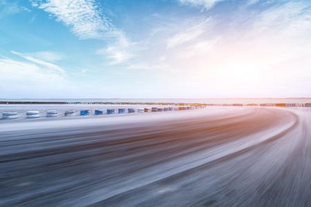 Movimiento borrosa pista de carreras de asfalto y río con hermosas nubes al atardecer