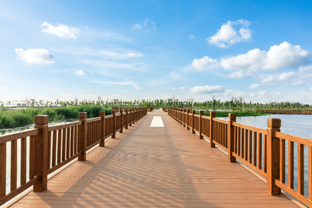 Empty boardwalk and beautiful clouds in city park Stock Photo