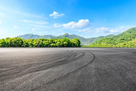 Terrain de course d'asphalte et paysage naturel de montagnes vertes