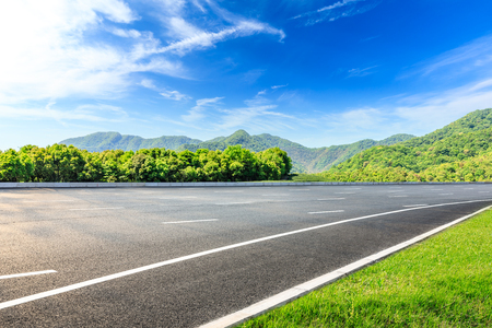 Country road and green mountains natural landscape under the blue sky Standard-Bild