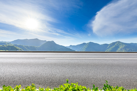Country highway and green mountains natural landscape under the blue sky Standard-Bild