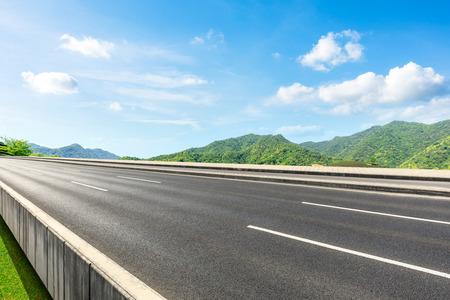 Landstraße und Naturlandschaft der grünen Berge unter dem blauen Himmel