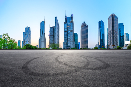 Asphalt race track ground and modern skyline and buildings in Shanghai at night,panoramic view