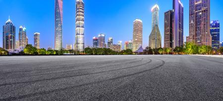 Pista de carreras de asfalto y horizonte moderno y edificios en Shanghai por la noche, vista panorámica