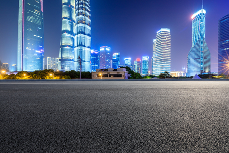 Shanghai modern commercial office buildings and empty asphalt highway at night