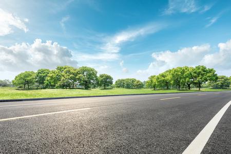 Landweg en groen bos natuurlijk landschap onder de blauwe hemel Stockfoto