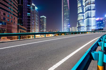 Shanghai moderne commerciële kantoorgebouwen en lege asfaltweg 's nachts Stockfoto