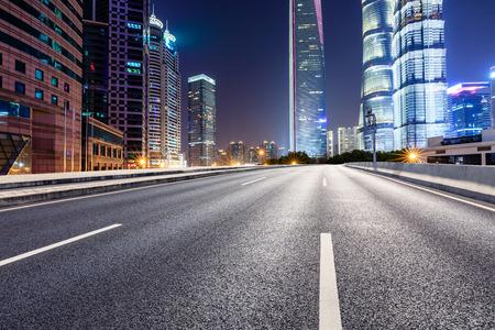 Modernos edificios de oficinas comerciales de Shanghai y autopista de asfalto vacía en la noche