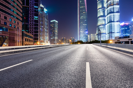 Shanghai moderni edifici per uffici commerciali e autostrada asfaltata vuota di notte