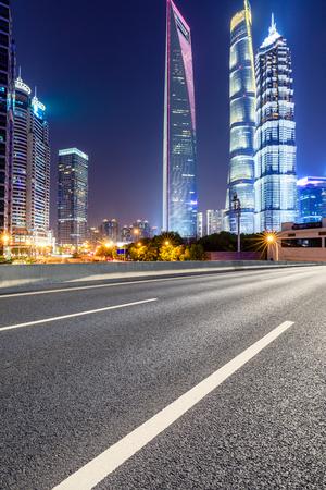 Moderne Geschäftsbürogebäude Shanghais und leere Asphaltautobahn nachts