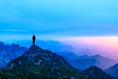 Man staande op de top van de berg, conceptuele scene Stockfoto
