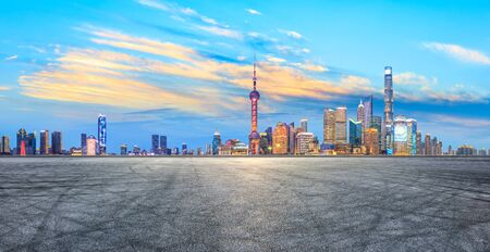 Asphalt race track ground and modern skyline and buildings in Shanghai at night, panoramic view