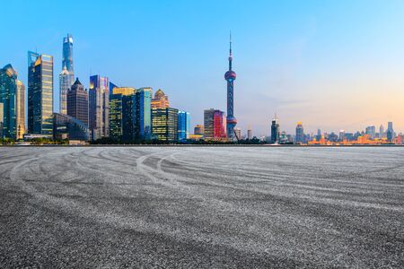 Asphalt race track and modern skyline and buildings in Shanghai at sunset