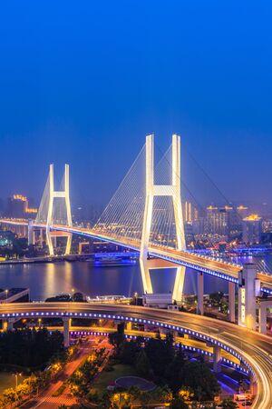 Hermoso puente Nanpu en la noche, cruza el río Huangpu, Shanghai, China