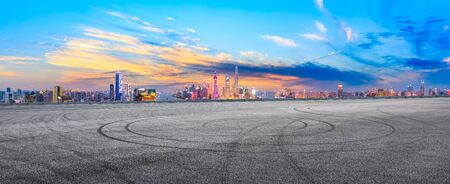 Empty race track and modern city skyline in Shanghai at sunset,China