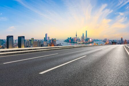 Empty asphalt highway and modern city skyline in Shanghai at sunset,China