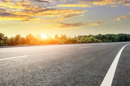 Asphalt highway and green forest with beautiful cloud landscape at sunset