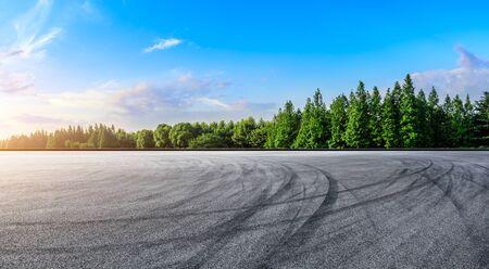 Asphalt race track and green woods nature landscape at sunset Imagens