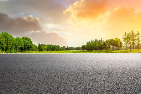 Country asphalt road and green woods nature landscape at sunset